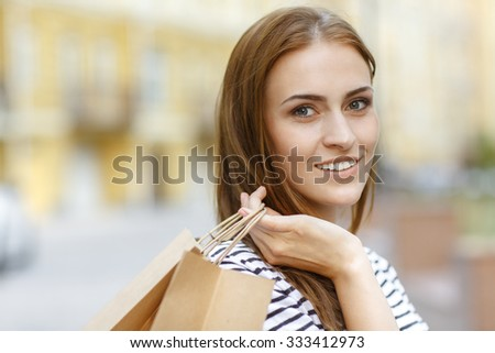 Love shopping. Close up shot of a beautiful dark haired female smiling to the camera with her purchases in her hand - stock photo