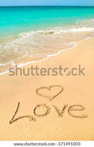 Love sign on the beach with turquoise water - stock photo