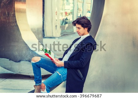 Love Story. American college student, wearing fashionable long coat, jeans, sitting against metal mirror wall on campus in New York, reading red book with white rose. Instagram filtered effect.  - stock photo