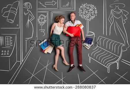 Love story concept of a romantic couple on shopping against chalk drawings background. Young happy couple standing together with shopping bags in a shopping mall. - stock photo
