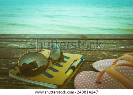 love summer decorate with eyeglasses and  note book on wooden floor on the blue sea. - stock photo