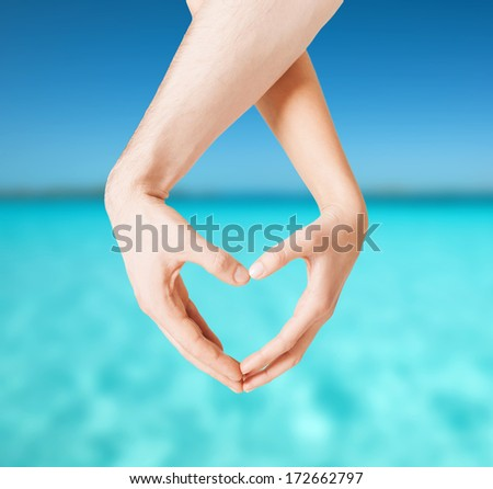 love, summer holidays and vacation concept - close up of woman and man hands showing heart shape - stock photo
