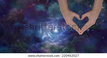 Love the Universe Banner -   Woman's hands making a heart shape with deep space nebula and clouds in background  - stock photo