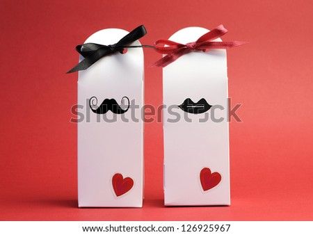 Love theme his and hers romantic white Valentine or wedding gift boxes against a red background. - stock photo