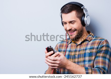 Love this music. Handsome young man in headphones holding mobile phone and smiling while standing against grey background - stock photo