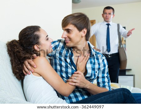 Love triangle: adult husband, happy spanish wife and lover at domestic interior - stock photo