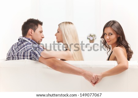 Love triangle. Beautiful young women holding hands with men sitting near his girlfriend - stock photo