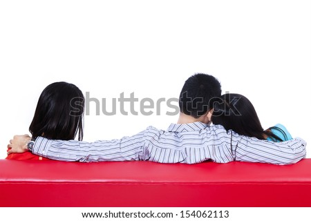 Love triangle of two woman and one man sitting on red sofa. Isolated on white - stock photo