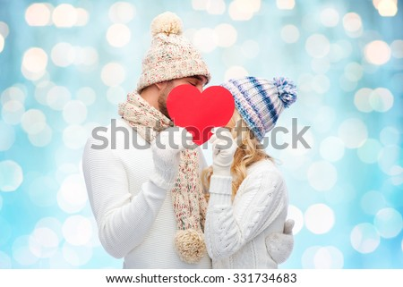love, valentines day, couple, christmas and people concept - smiling man and woman in winter hats and scarf hiding behind red paper heart shape over blue holidays lights background - stock photo