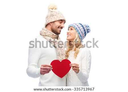 love, valentines day, couple, christmas and people concept - smiling man and woman in winter hats and scarf holding red paper heart shape - stock photo