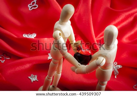 Love wooden figurines on silk red background holding a heart shaped blood vial. Vintage chic style. Soft warm tender feelings. Holiday card for valentine's day. Surrounded by butterflies - stock photo