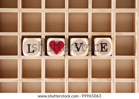 love word construction with letter blocks / cubes, a heart and a shallow depth of field - stock photo