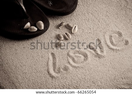 Love Written on Sand with Slipper and Shells - stock photo