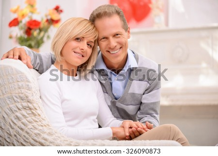 Love you tender. Pleasant happy adult couple sitting on the couch and bonding to each other while expressing warm feelings - stock photo