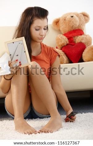 Lovelorn teenage girl sitting on floor at home, looking sad. - stock photo