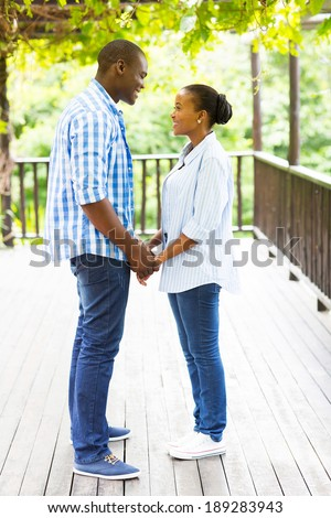 lovely african american couple holding hands outdoors - stock photo
