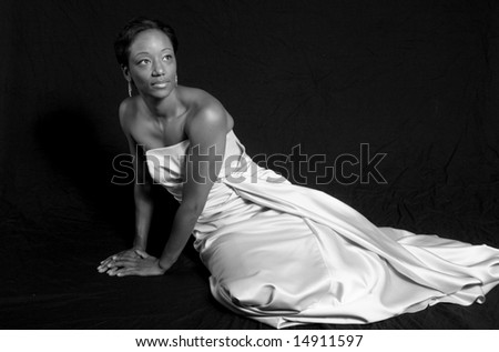 Lovely African American woman reclining in a formal, white dress, in black and white - stock photo