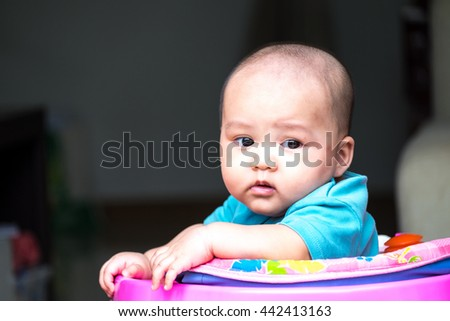 lovely asian baby on car walker toy  - stock photo