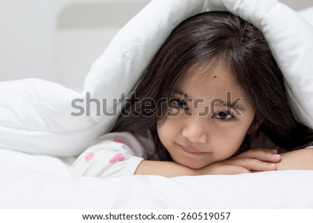Lovely Asian child laying down on the bed - stock photo