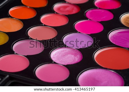 Lovely assortment of bright colors for challenging make-up. Various tints of red and pink. Lipstick palette is the best present for girl or woman. - stock photo