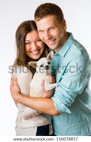 Lovely attractive couple and dog together, studio shot, white background - stock photo
