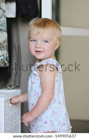 Lovely baby girl plays with white storage basket in a big wardrobe - stock photo