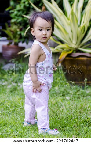 Lovely baby girl standing and trying to walk - stock photo