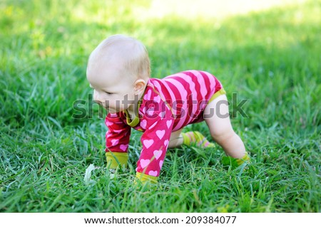 Lovely baby girl  trying to get up outdoor on the green lawn at the warm day - stock photo