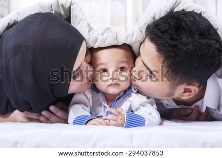 Lovely baby with happy parents kissing the baby under the blanket on the bed - stock photo