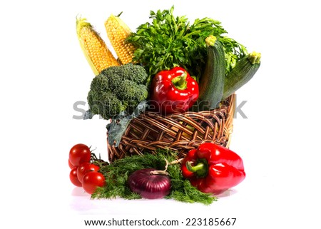 Lovely basket with fresh vegetables including pepper lettuce tomatoes corn broccoli and cucumber is pleasure for every vegetarian. Isolated on white background - stock photo