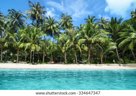 Lovely Beach with Turquoise Water and Green Palm Trees on a Tropical Island - stock photo