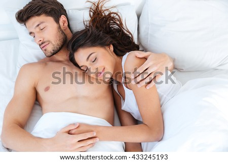 Lovely beautiful young couple sleeping on their bed at home - stock photo