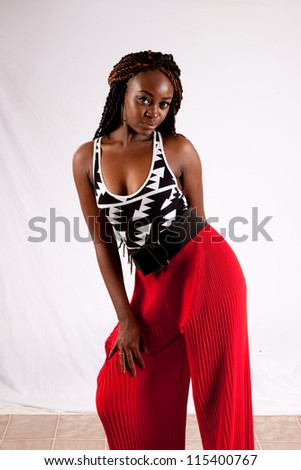 Lovely black woman in red pants, leaning forward at the hips and looking at the camera with a friendly, coy expression - stock photo