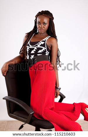 Lovely black woman kneeling backwards in a chair and resting her arm on the back of the chair while she looks at the camera with a playful expression - stock photo