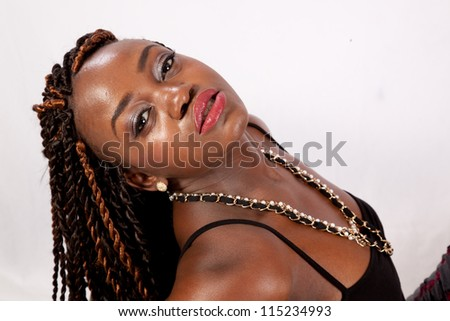 Lovely black woman reclining and leaning back, with a sexy, serious look for the camera - stock photo