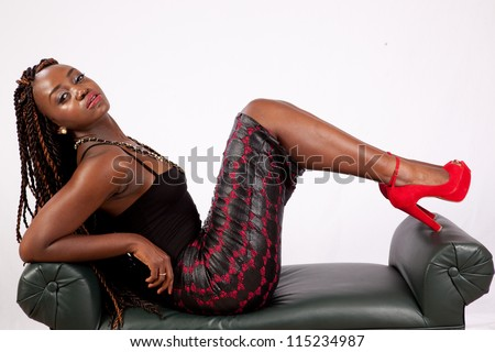 Lovely black woman reclining on a bench with her feet up, and with a serious, sexy look for the camera - stock photo
