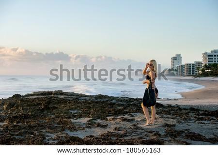 lovely blond female in bikini ready for beach at sunrise near rocky section of florida atlantic coast - stock photo