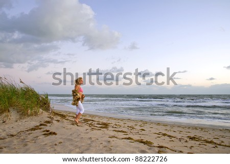 lovely blond female on florida beach with windy morning surf - stock photo