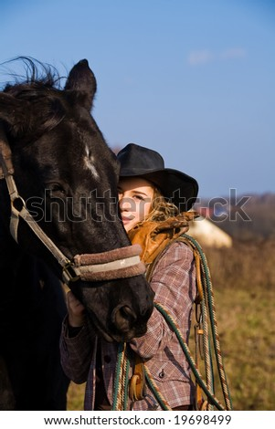Lovely blond woman in a hat standing by horse in a field - stock photo
