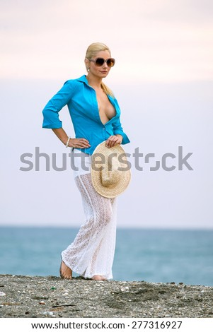 lovely blonde female in open blouse at beach on cloudy, windy morning - stock photo