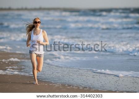 lovely blonde female takes morning jog along florida beach - stock photo