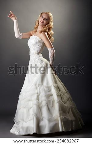 Lovely blonde posing in elegant wedding dress - stock photo