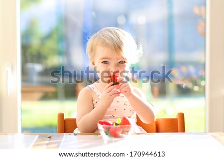 Lovely blonde toddler girl in summer dress eating strawberries sitting indoors in the kitchen next to a big window with garden view - stock photo