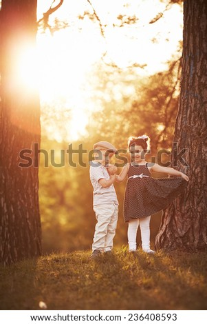 lovely boy and girl on sunset - stock photo