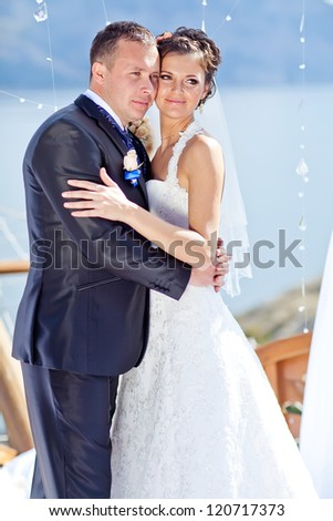 Lovely bride and groom holding hands while facing each other and smiling - stock photo