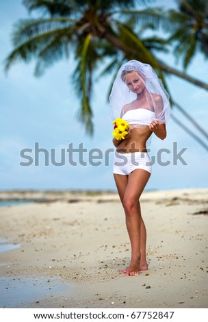 Lovely bride on the beach near the sea - stock photo