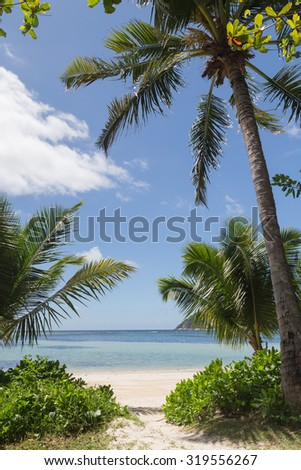 Lovely bright vertical sea landscape with white sand, with tropical plants and clean clear waters of the Indian Ocean, Seychelles - stock photo