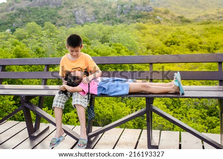 Lovely brother and sister sitting together - stock photo