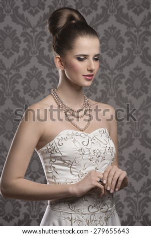 lovely brunette with elegant hair-style and dress, stylish make-up and pearls jewellery  - stock photo