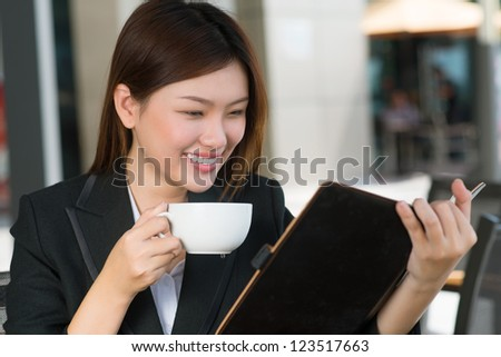Lovely business woman reading notes in her organizer - stock photo